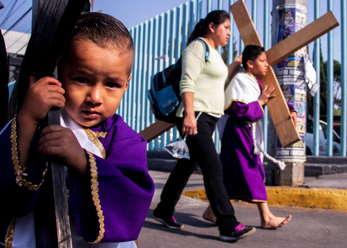 """Personas de todas las edades cargan cruces como manda en viernes santo, se les conoce como """"nazarenos""""."""